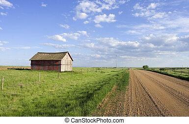 Rural scene - Farmers shed in the fields along side a gravel...