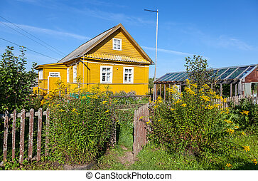 Rural scene with yellow flowers and wooden house