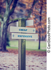 Rural signboard with two signs saying - Cheap - Expensive - pointing in opposite directions.