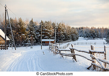 Rural snowy covered road with wooden fence along is in Russian village in winter season. Russia