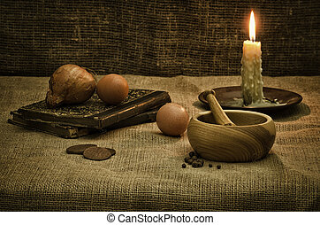 Rural still life with mortar,candle,books and eggs