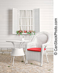 Rural summer recreation area. Wicker furniture. Flower bed by the window.
