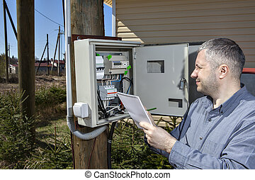 Rural Technician Taking Reading Of Electric Meter in the countryside.
