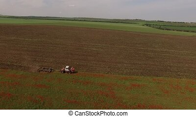 Rural Tractor Cutting Poppy Fields - AERIAL VIEW. This is a...