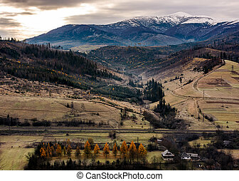 rural valley at the foot of snowy mountain. hills with...