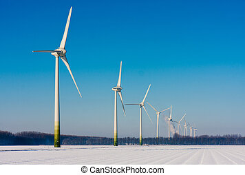Rural winter landscape in the Netherlands with big windturbines