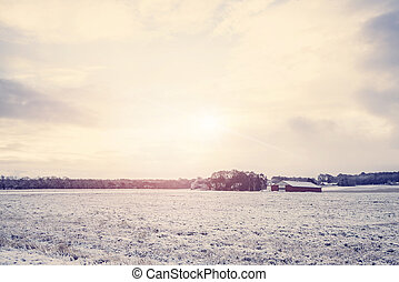 Rural winter landscape with a red barn