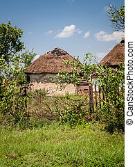 Rural yard with old farmhouse with thatched roof