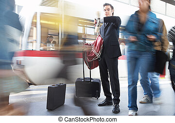 rush - businessman at the train station looking at his watch