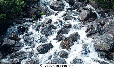 Rushing foamy water of the rocky waterfall