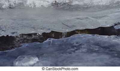 Rushing Water in Frozen River Ice - Frigid river water...