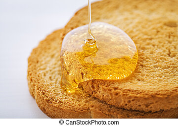 two toasted slices covered with honey leaking