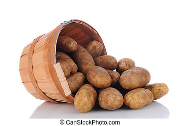 A basket full of russet potatoes on its side spilling onto a white surface with reflection. Horizontal format.
