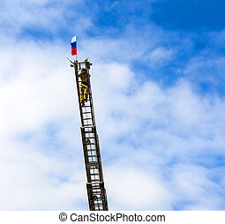 Fireman on a long fire escape against the blue sky raises the flag