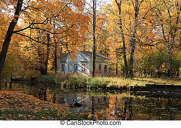 Russia, St. Petersburg, October 2, 2021, Alexander Park. In the photo - an autumn pond with fallen leaves and a children's house. The beauty of the October forest in Russian forests,selective focus