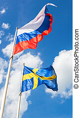 Russian and Sweden flags waving against the blue sky