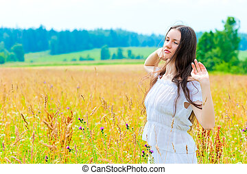Russian beautiful woman in field with flowers