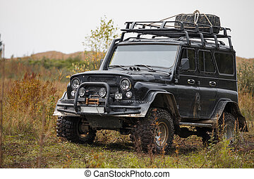 Russian black off road car UAZ in a meadow