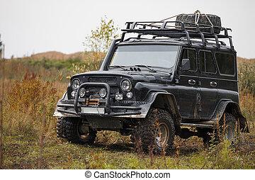 Russian black off road car UAZ in a meadow