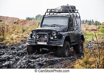 Russian black off road car UAZ in mud