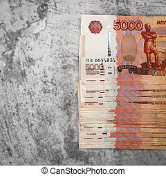 Russian cash banknotes of five thousand rubles, the bundle hangs on a gray background.