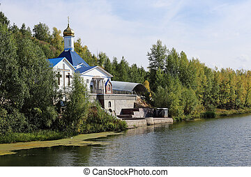 Russian Church on the shore of a pond in autumn