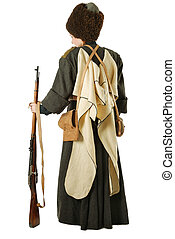 Young woman is wearing vintage uniform of Russian foot Cossack in time First World War. Russian Cossack is standing back. She is dressed in woolen greatcoat, fur cap and hood. She has bags and a rifle.
