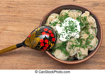 Russian cuisine: dumplings with sour cream and dill.
