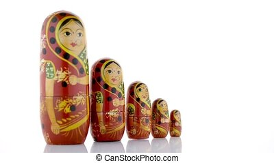 Russian dolls on white reflective background.