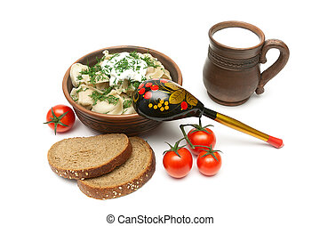 Russian dumplings in a clay bowl, bread, milk and tomatoes on a