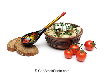 Russian dumplings with sour cream in a clay plate on a white background