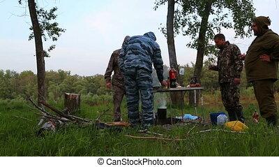 russian fishermen drink vodka around campfire at night