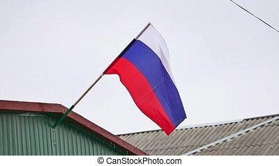 Russian flag fluttering in the wind on the roof - Russian...
