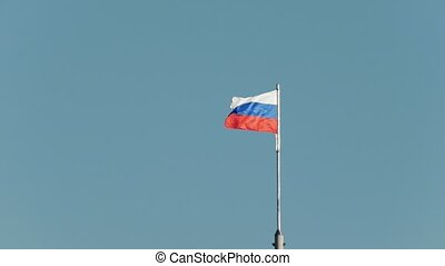 Russian flag flutters in the wind in front of blue sky