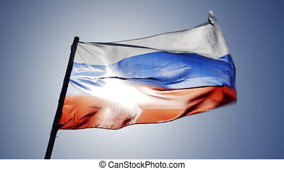 russian flag flying in slow motion and back lit by the sun.