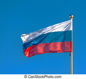 Russian flag on a background blue sky.