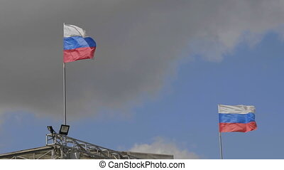 Russian flag on the flagpole waving in the wind against a blue sky with clouds cinemagraph