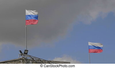 Russian flag on the flagpole waving in the wind against a blue sky with clouds