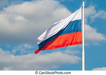 Russian flag waving in the wind against the blue sky,