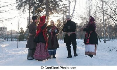 Russian folk - a group of people in traditional costumes are dancing in a circle and clappping