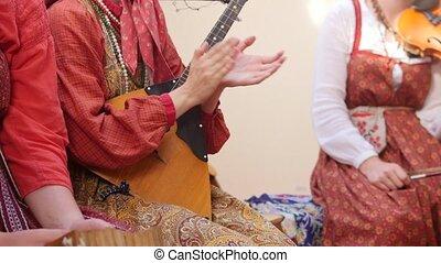 Russian folk ensemble - woman make music by clapping hands