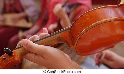 Russian folk group musician - woman play violin, close up