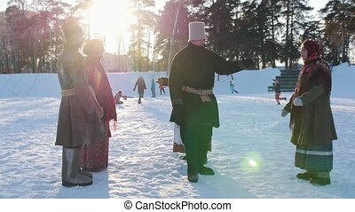 Russian folk - man is dancing traditional dance in a circle of women in winter
