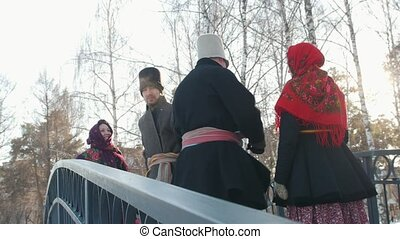 Russian folk - men in traditional costumes dance on the bridge