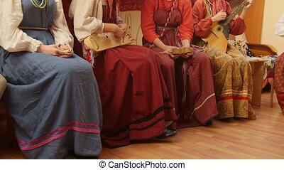 Russian folk musical group -girls in traditional costumes plays musical instruments