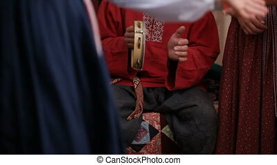 Russian folk musical group - man in traditional costumes plays musical instruments - tambourine, slow-motion