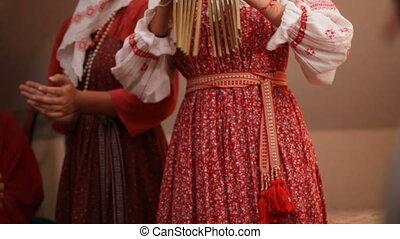 Russian folk musical group - woman in traditional costumes plays musical instruments - ratchet, slow-motion