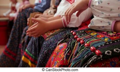 Russian folk musical group - women in traditional costumes sitting on bench