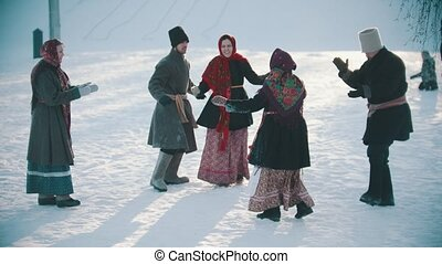 Russian folklore - funny russian people in traditional costumes are having fun on a sunny day