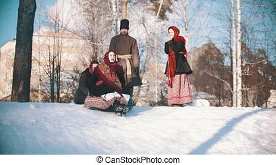 Russian folklore - people in traditional costumes are rolling a beautiful woman off a hill
